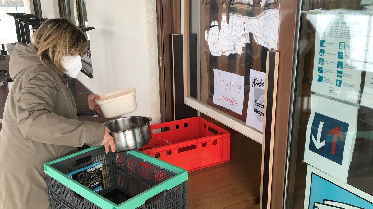 Frau mit Mundschutz mit Kisten und Töpfen: Braten-to-go vom Sportverein Deiningen