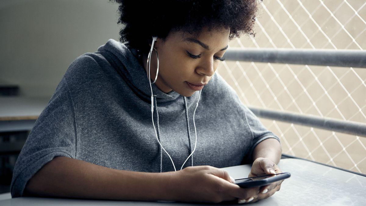 Eine junge Frau schaut auf ihr Smartphone und hört etwas mit Kopfhörern.