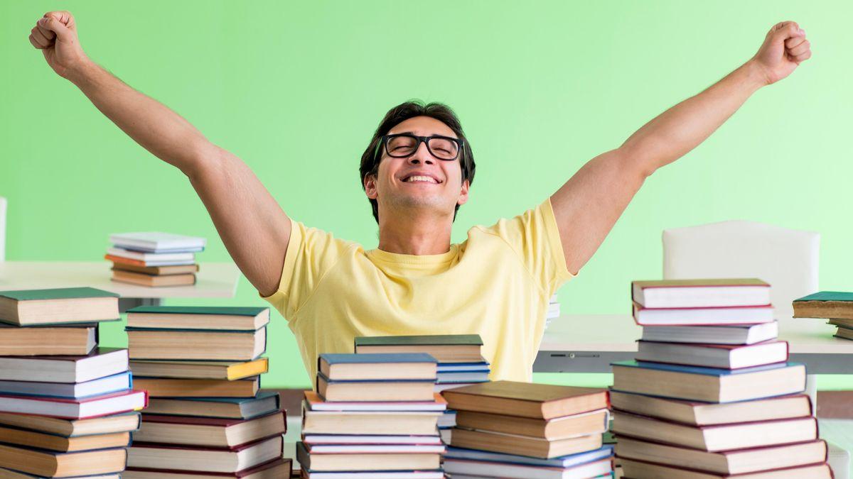 Student hat stapelweise Literatur auf dem Schreibtisch