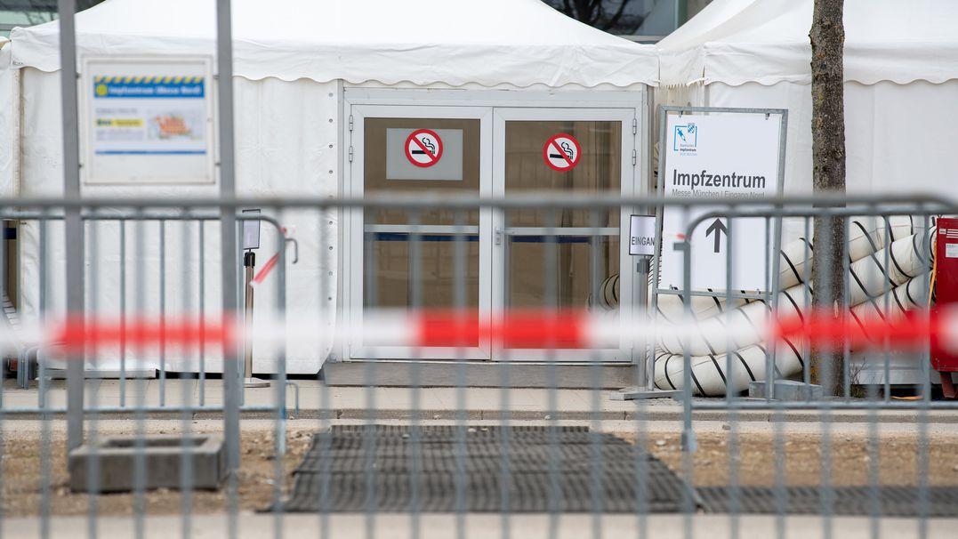 Ein Schild auf dem Gelände der Messe München zeigt den Weg zum Eingang des Impfzentrums.