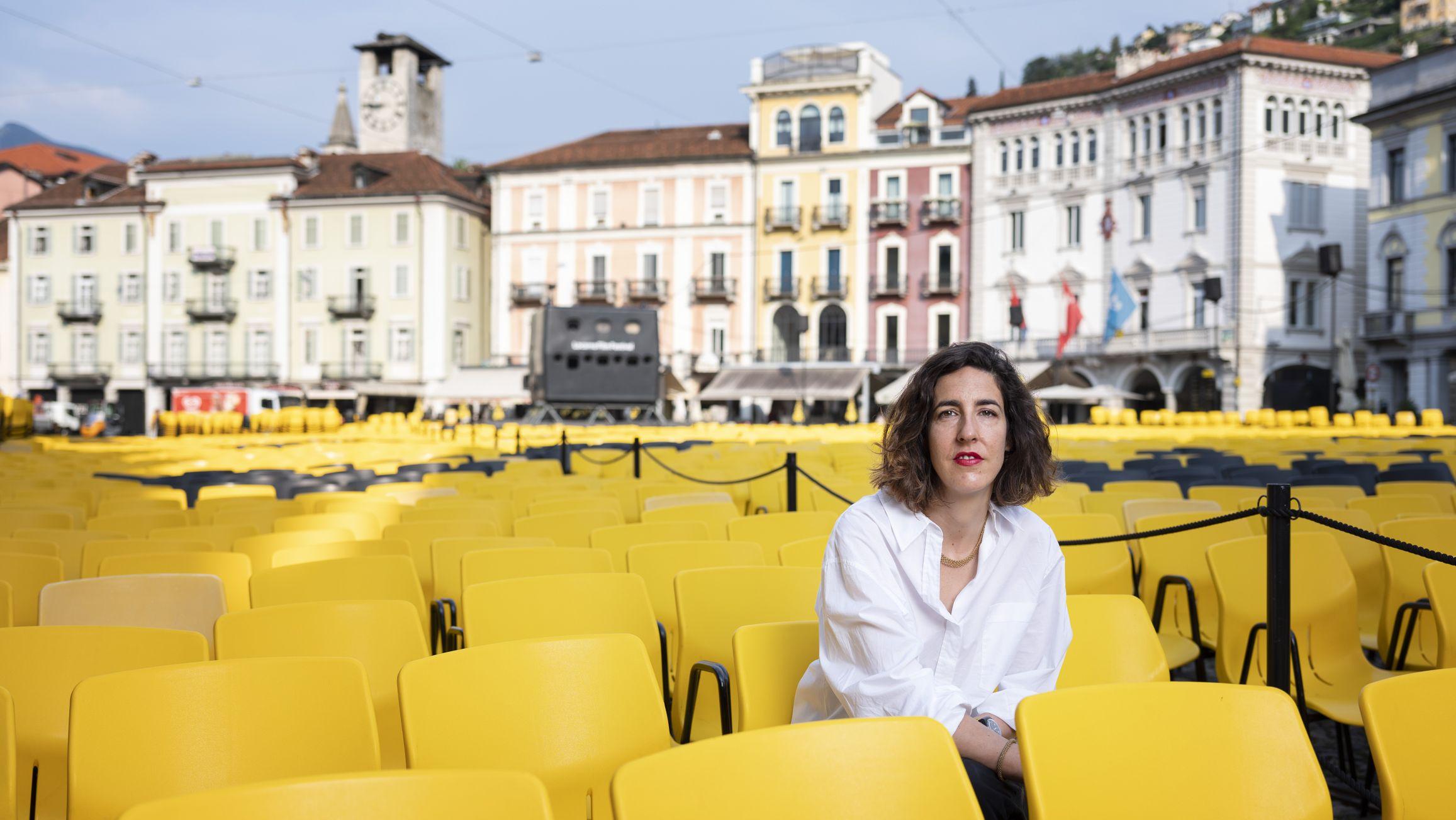 Lili Hinstin, neue künstlerische Leiterin des Filmfestivals in Locarno, sitzt in einem Meer aus gelben Stühlen auf der Piazza Grande