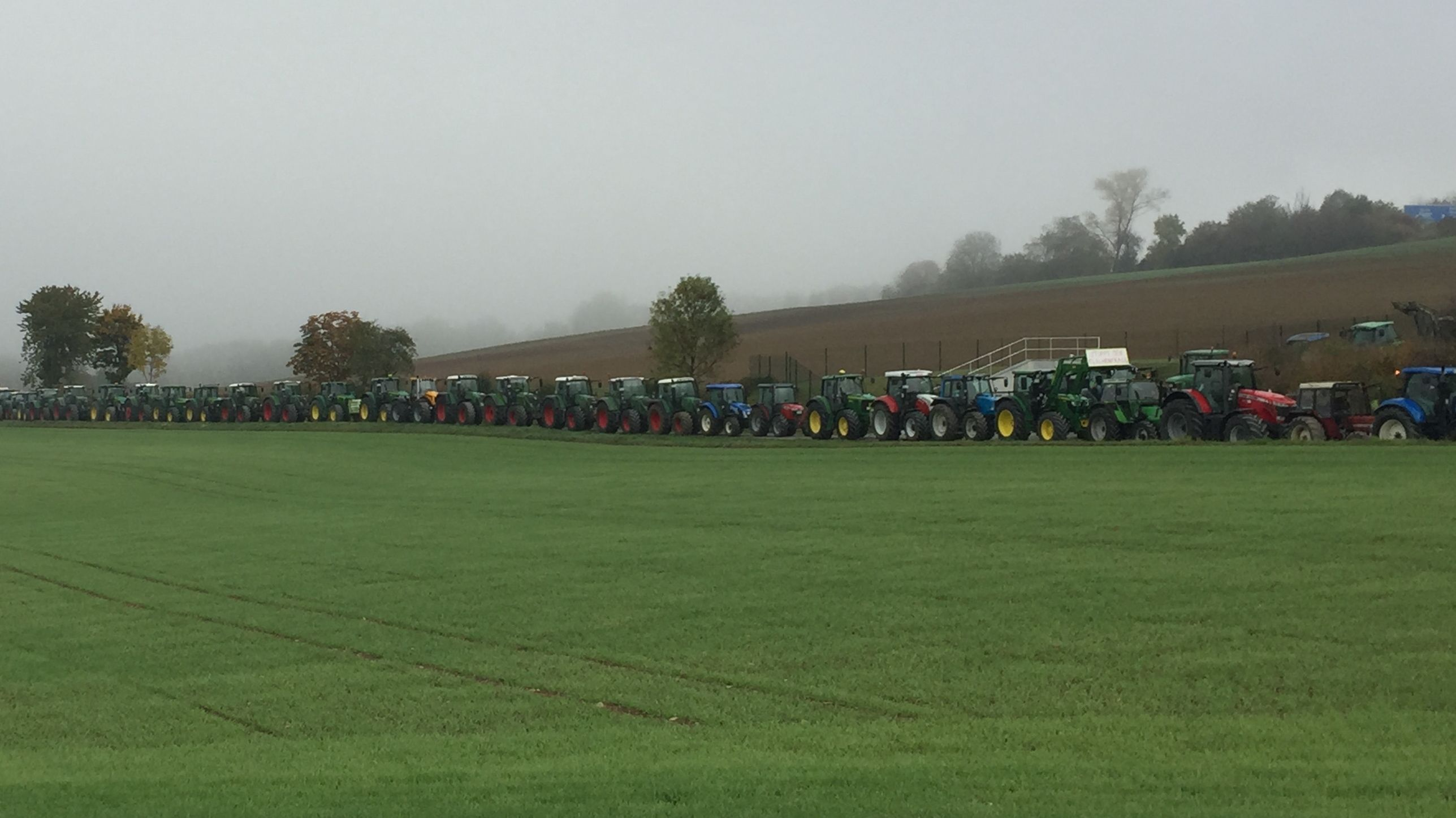 Viele Traktoren stehen auf einem Feldweg in Reih und Glied. Im Vordergrund ist eine Wiese zu sehen.