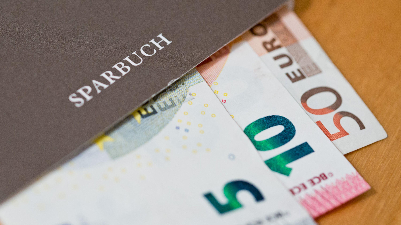 Euro-Geldscheine liegen in einem Sparbuch (Symbolbild)
