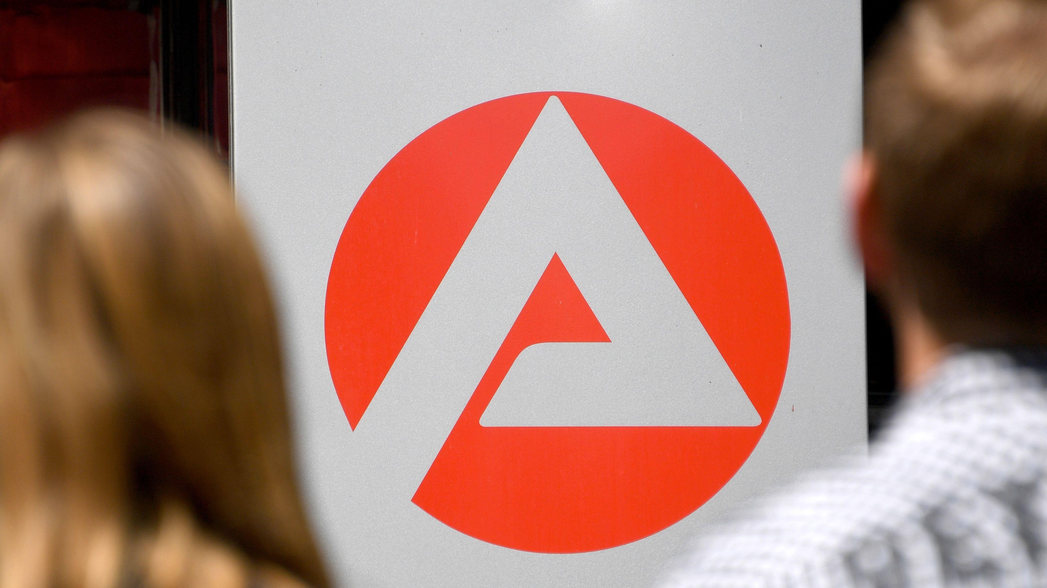 Zwei Menschen stehen vor dem Logo der Agentur für Arbeit