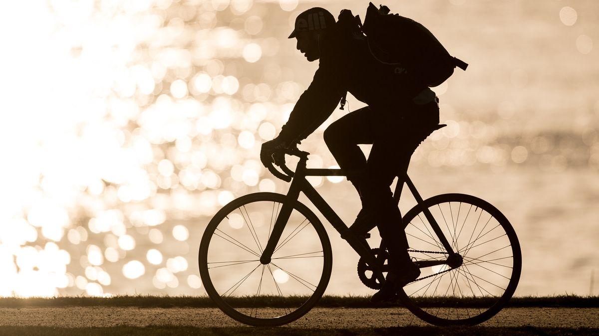 Ein Radfahrer fährt im Gegenlicht der tiefstehenden Sonne.