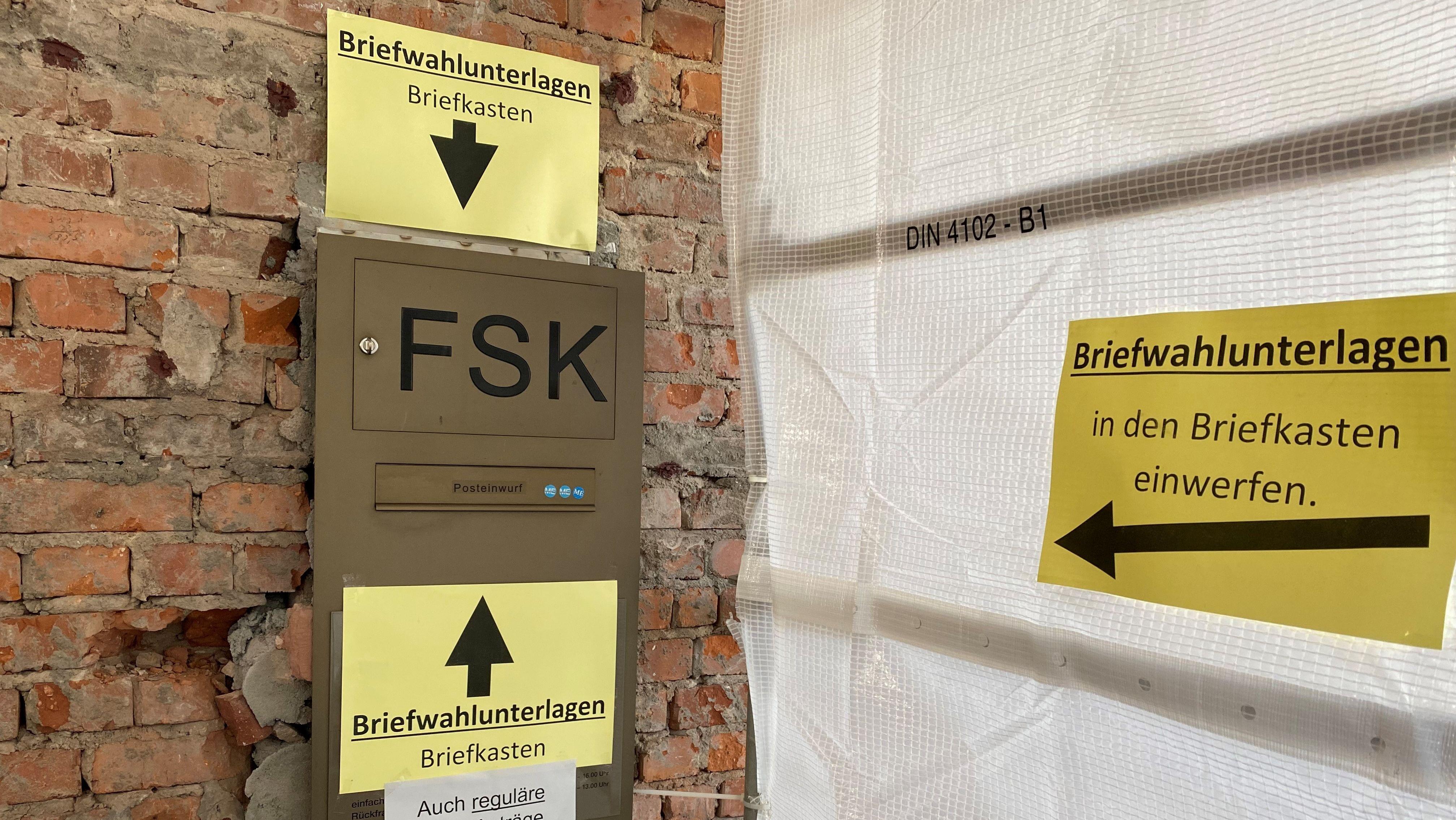 Briefkasten am Rathaus in Aschaffenburg mit Schildern, die darauf hinweisen, dass hier die Briefwahlunterlagen eingeworfen werden sollen.