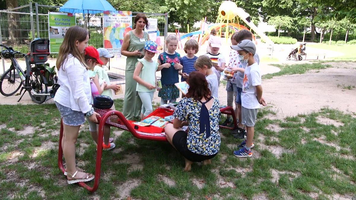 Zwei Beauftragte für Chancengleichheit mit einer Gruppe Kinder auf einem Spielplatz