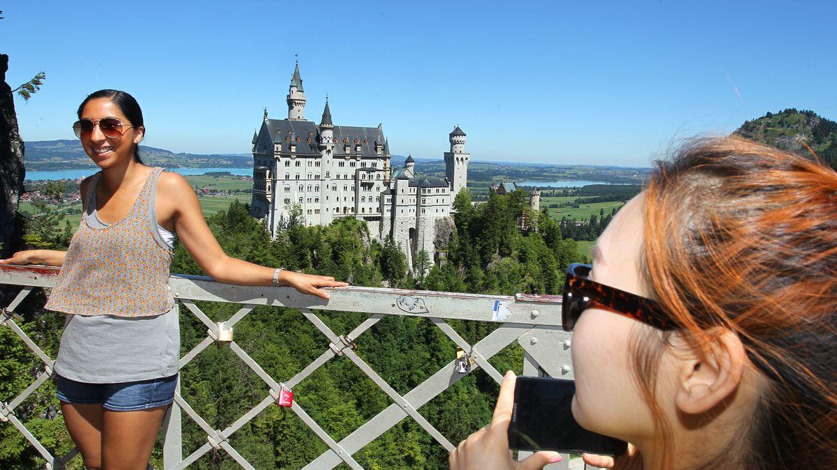 Touristen fotografieren einander vor dem Hintergrund des Schlosses Neuschwanstein