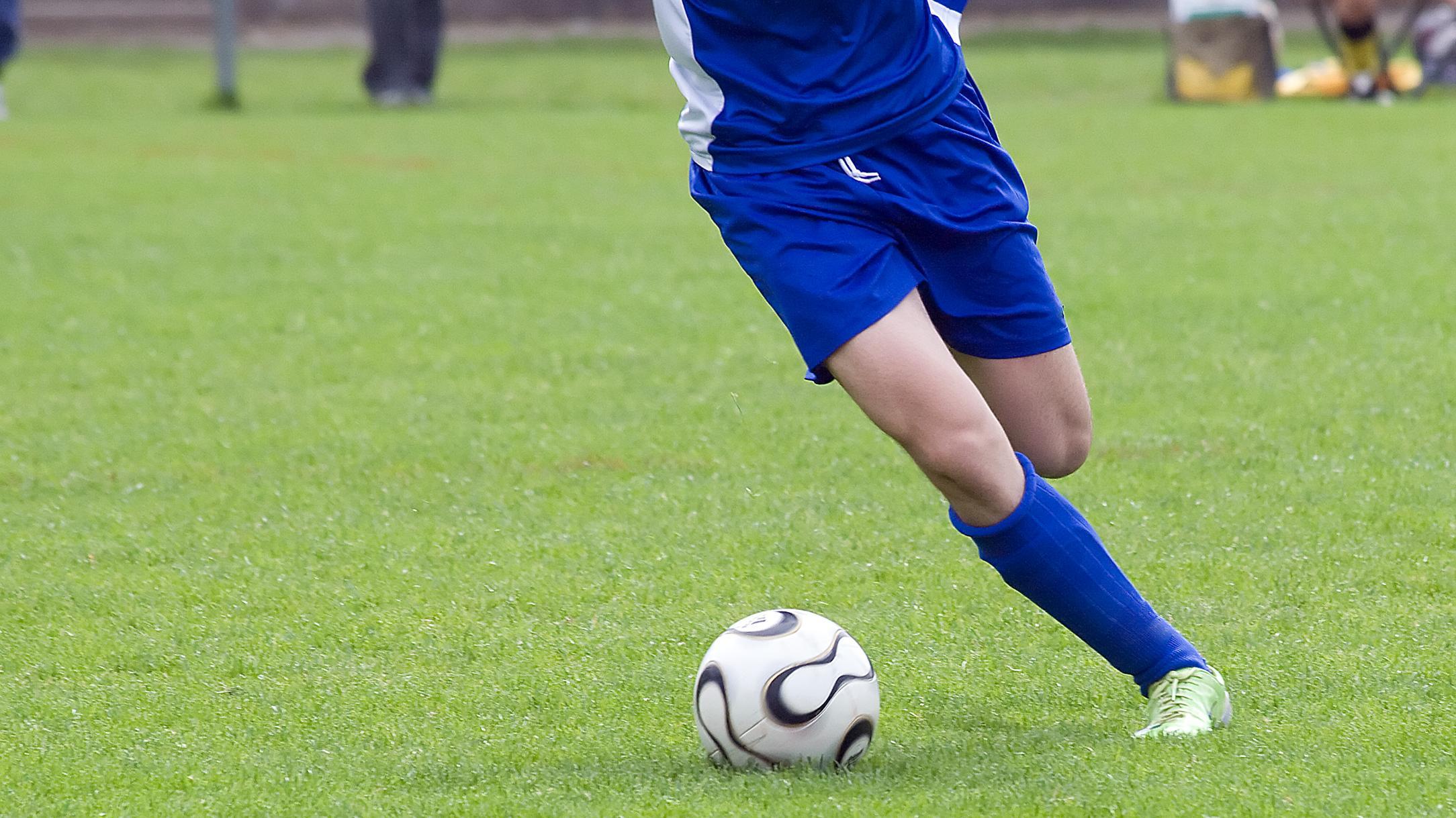 Die Beine eines Fußballspielers treten Richtung Ball