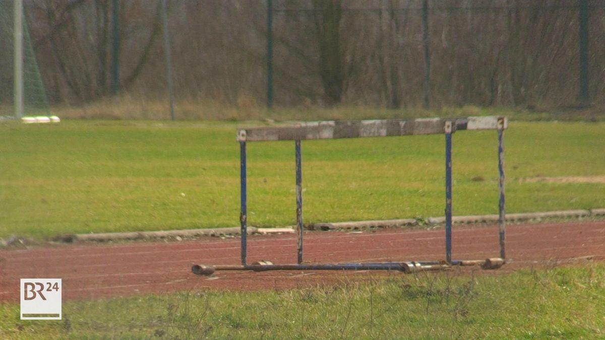 Blick auf einen verwitterten Sportplatz mit alter Hürde