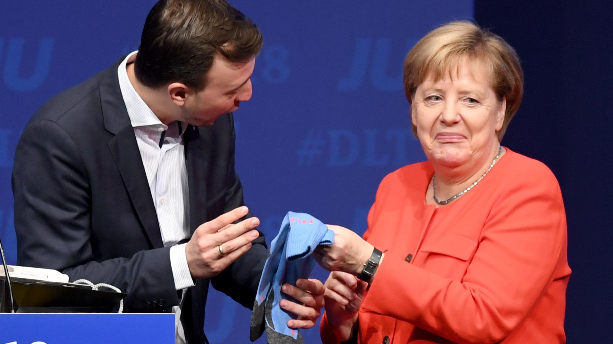 06.10.2018, Schleswig-Holstein, Kiel: Bundeskanzlerin Angela Merkel erhält beim Deutschlandtag der Jungen Union (JU) von Paul Ziemiak ein paar Socken als Geschenk.