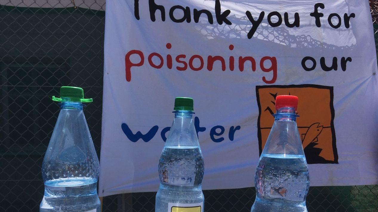 Symbolische Aktion mit Wasserflaschen mit Warnschildern vor Aktionsplakat in Ansbach Katterbach vor der US-Kaserne