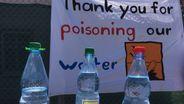 Symbolische Aktion mit Wasserflaschen mit Warnschildern vor Aktionsplakat in Ansbach Katterbach vor der US-Kaserne   Bild:BR/Claudia Mrosek