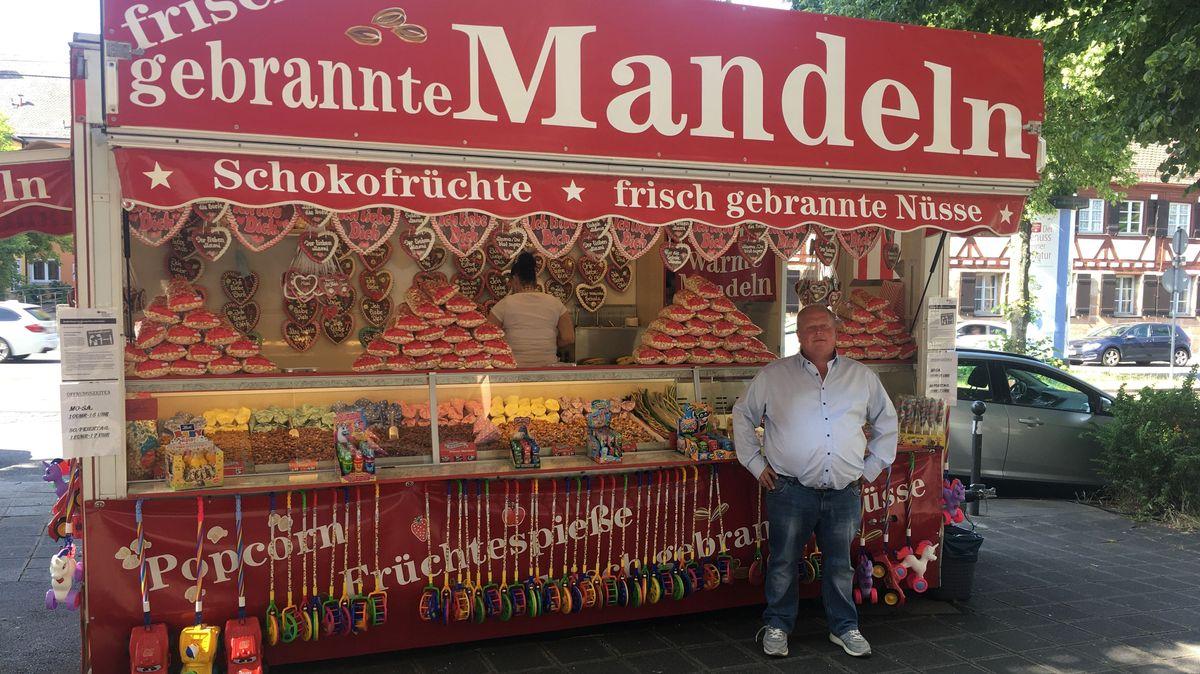 """Raimund Krug vor seinem roten Verkaufswagen mit der Aufschrift """"frisch gebrannte Mandeln"""", in dem auch viele Lebkuchenherzen hängen"""