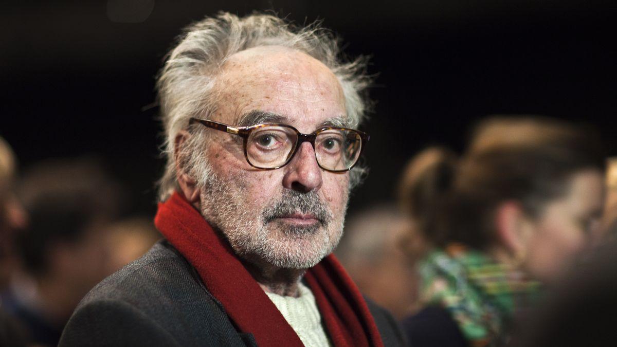 Ein Porträt von Jean-Luc Godard, mit Brille und rotem Schal