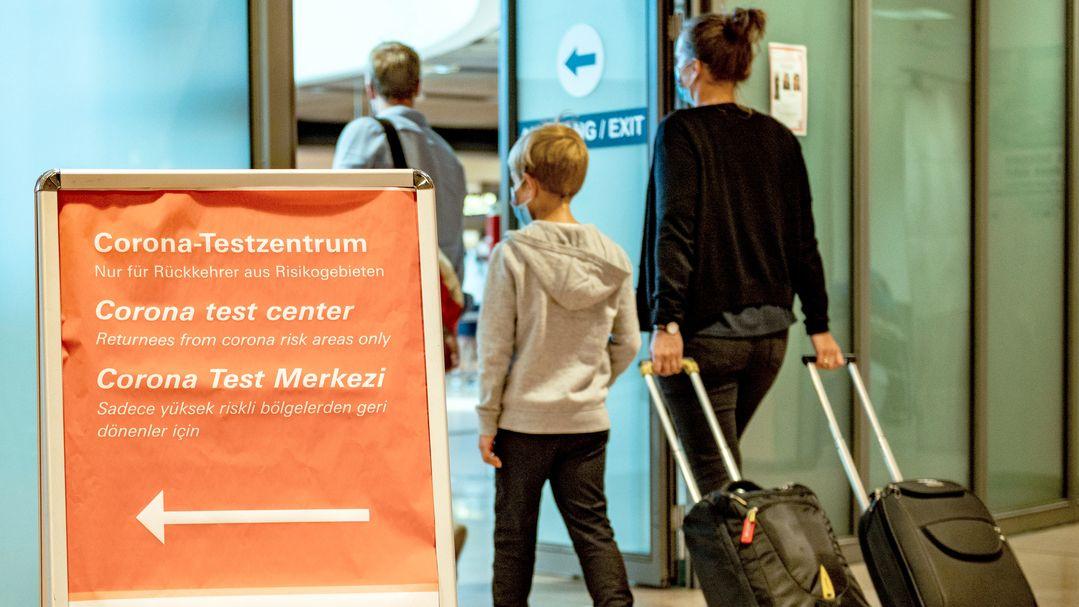 Reisende gehen aus dem Sicherheitsbereich eines Flughafens an einem Schild vorbei, auf dem die Richtung zum Corona-Testzentrum mit einem Pfeil angezeigt wird.