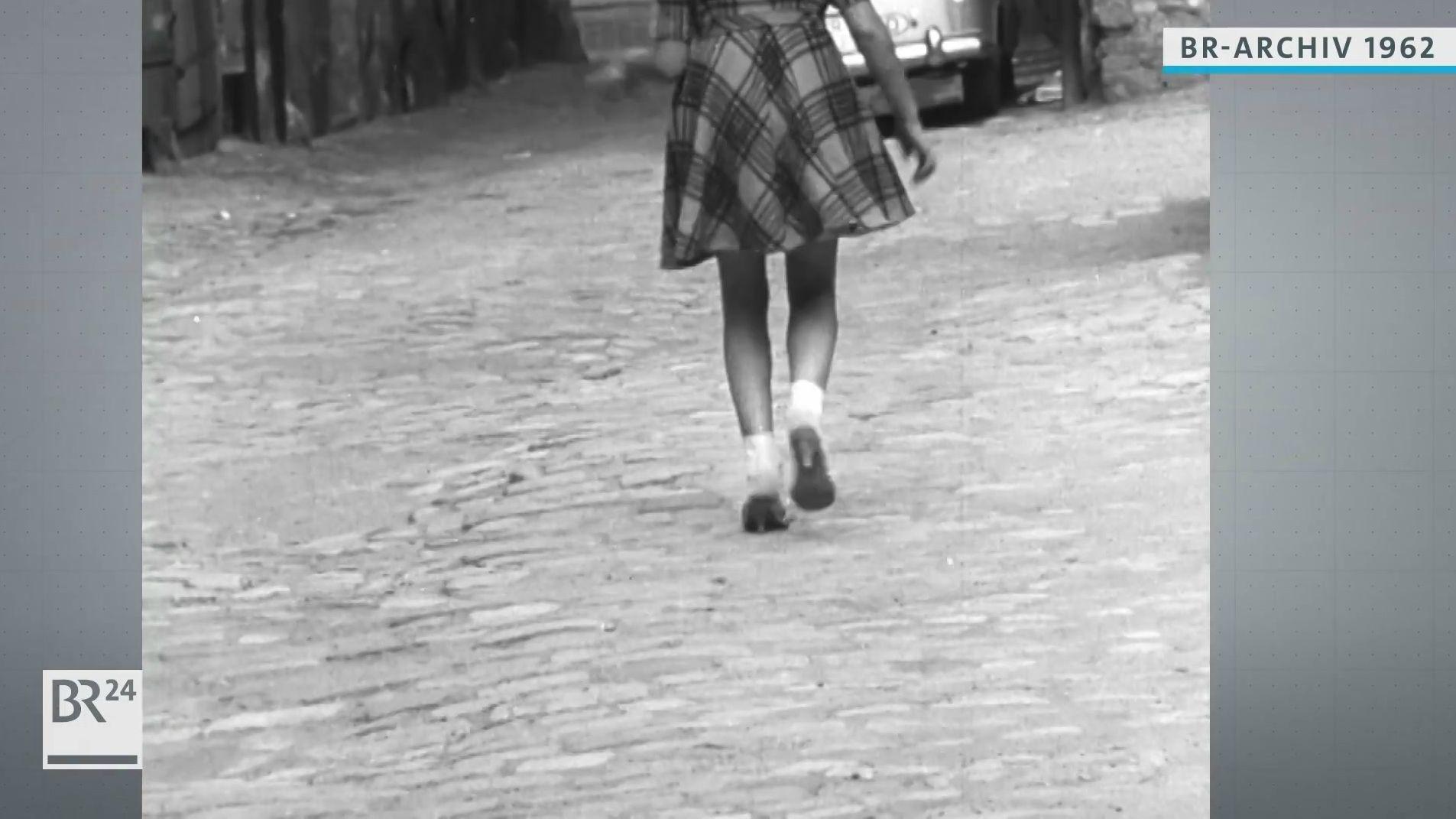 Dame spaziert auf Kopfsteinpflaster
