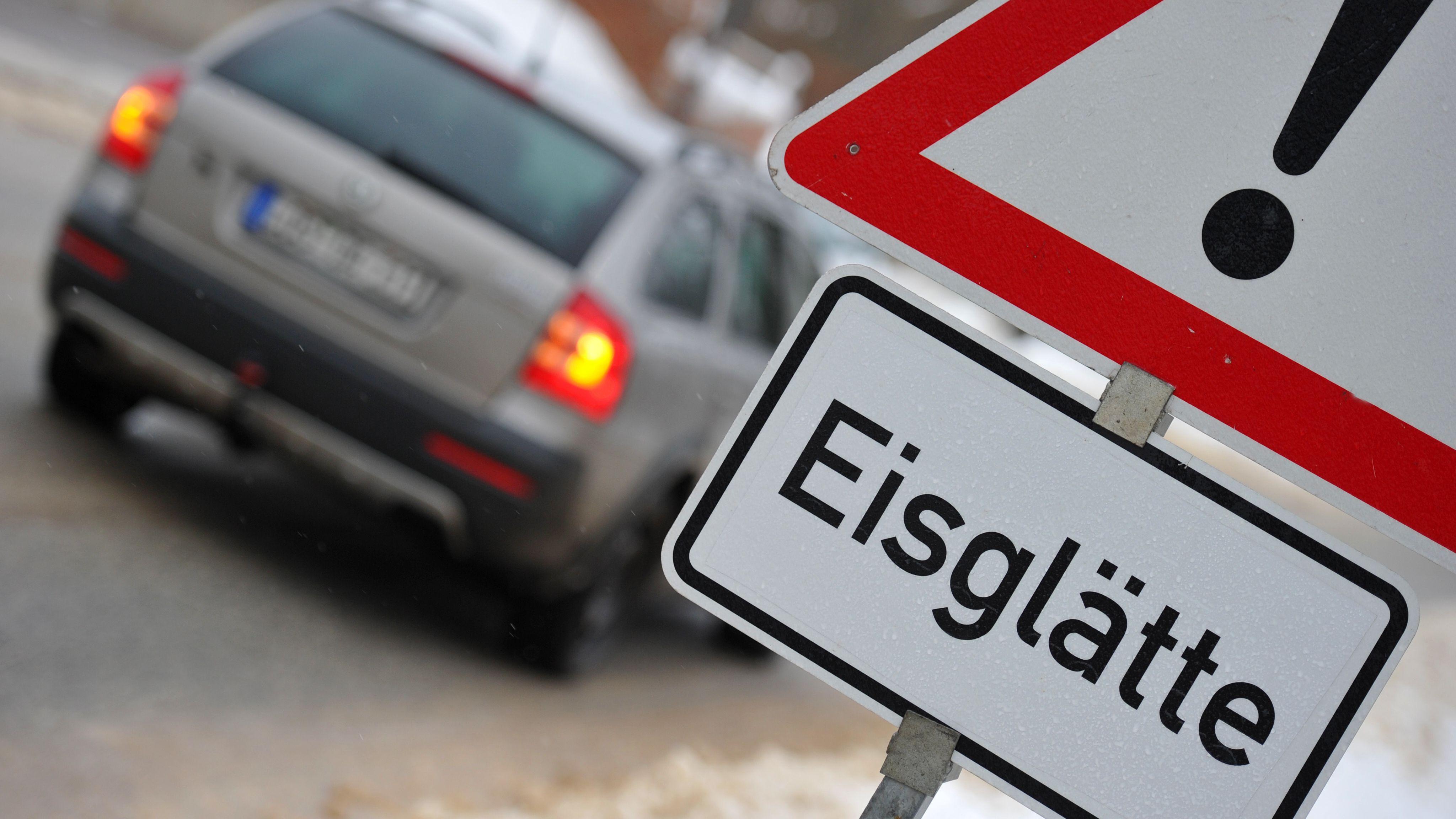 """Ein Warnschild mit der Aufschrift """"Eisglätte"""" steht an einer Straße."""
