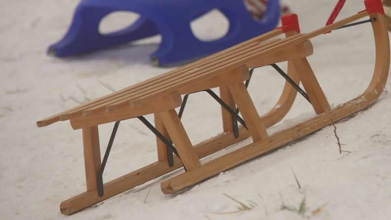 Ein Holzschllitten an einer Schnur