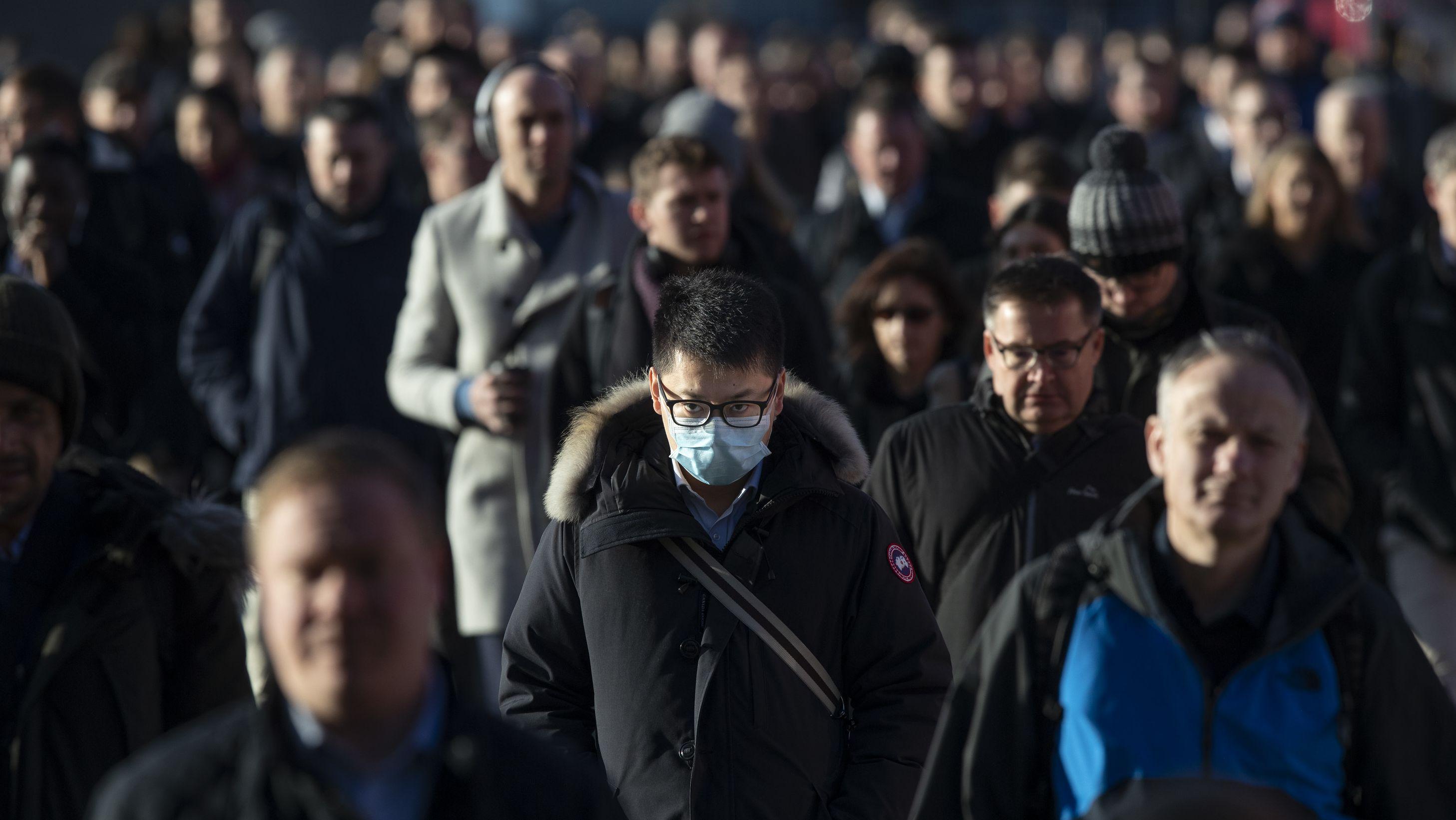 Mann mit Schutzmaske in einer Menschenmenge