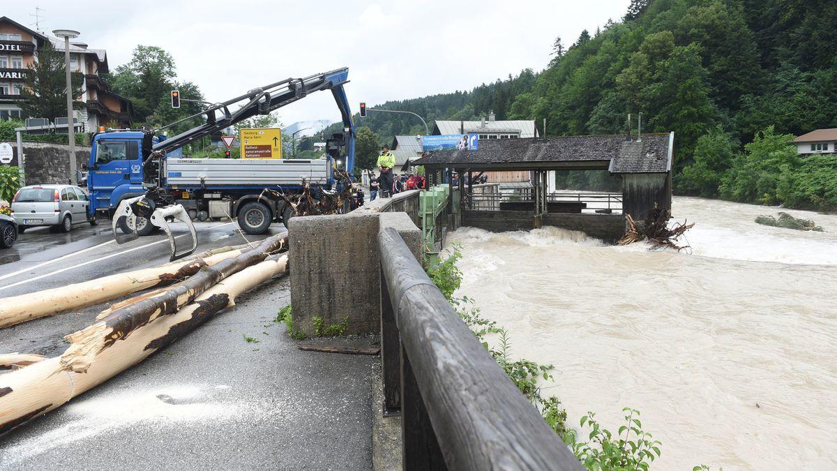 Aufräumen im Berchtesgadener Land: Einsatzkräfte ziehen einen Baumstamm aus dem Wasser.