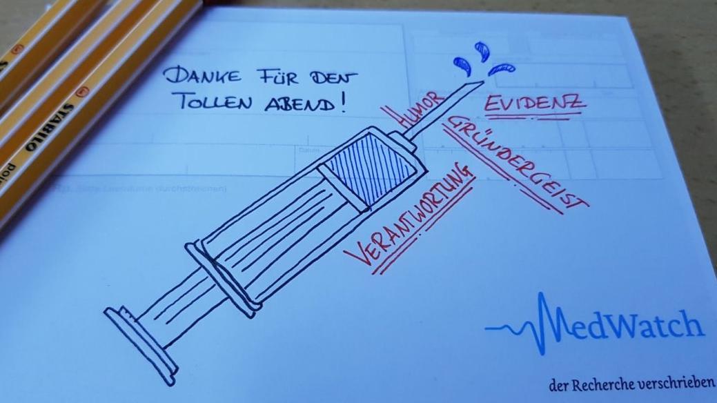 """Notiz auf einem Stammtisch von """"MedWatch"""". Zettel mit Zeichnung einer Spritze, Dank und Begriffen: Humor, Evidenz, Gründergeist und Veranwortung."""