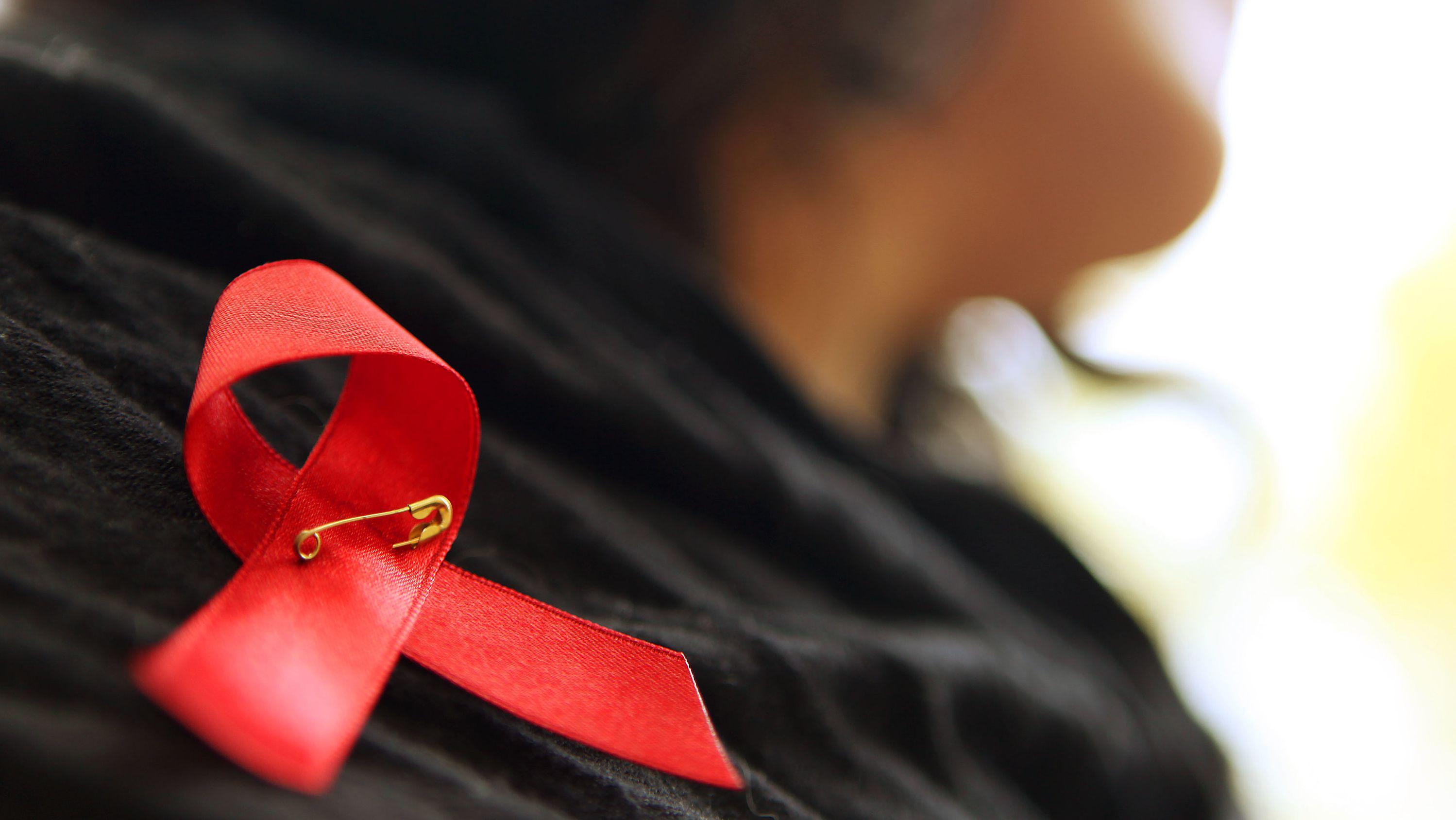 Frau trägt rote Schleife an der Schulter, die als Symbol der Solidarität mit HIV-Infizierten dient