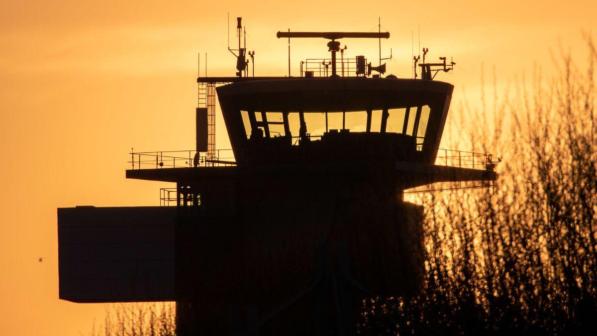 Der Schattenriss des Flugverkehrskontrollturms am Albrecht Dürer Flughafen hebt sich vor der untergehenden Sonne ab.