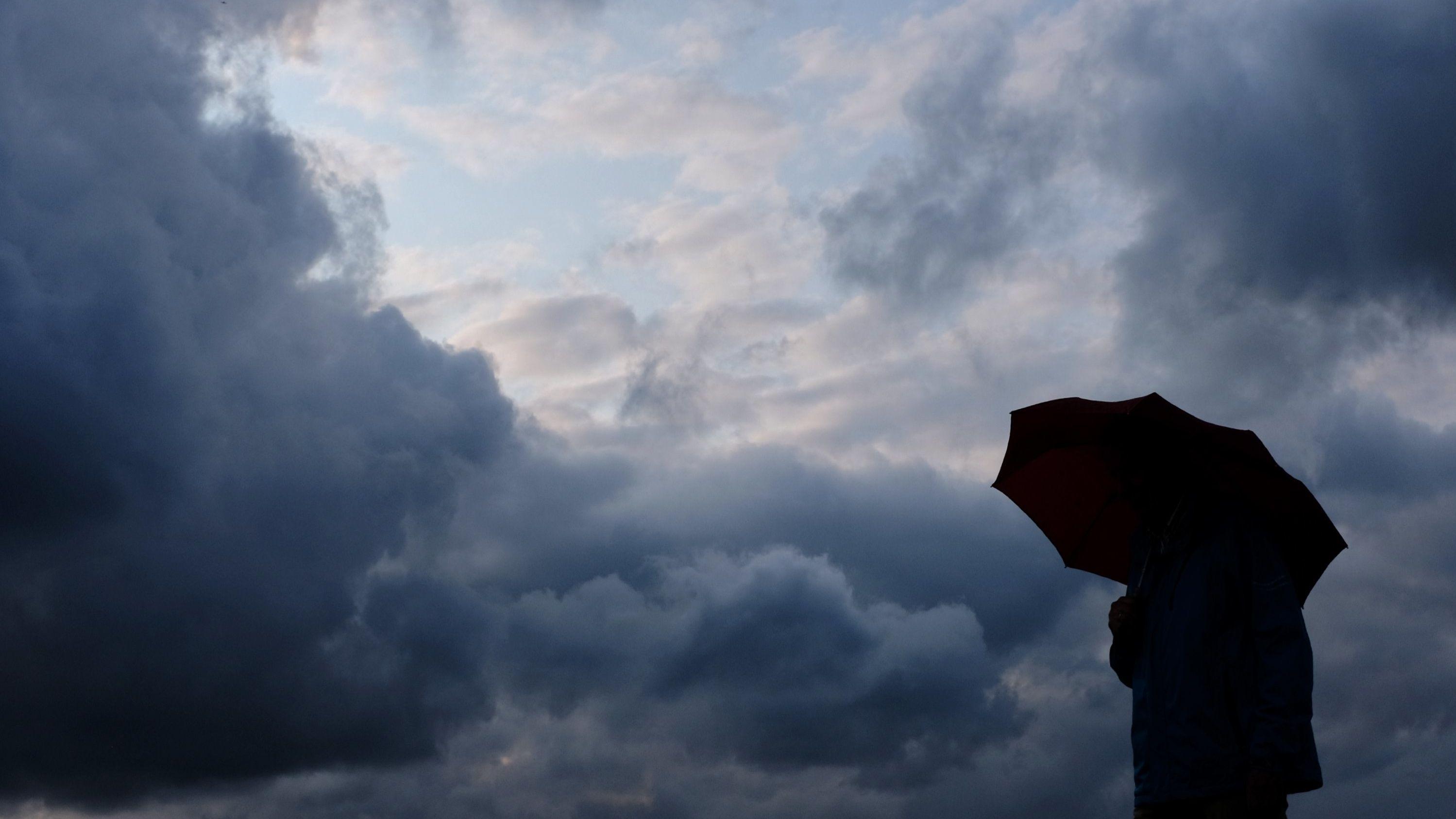 Ein Mann geht mit einem Regenschirm vor aufziehenden dunklen Wolken spazieren.