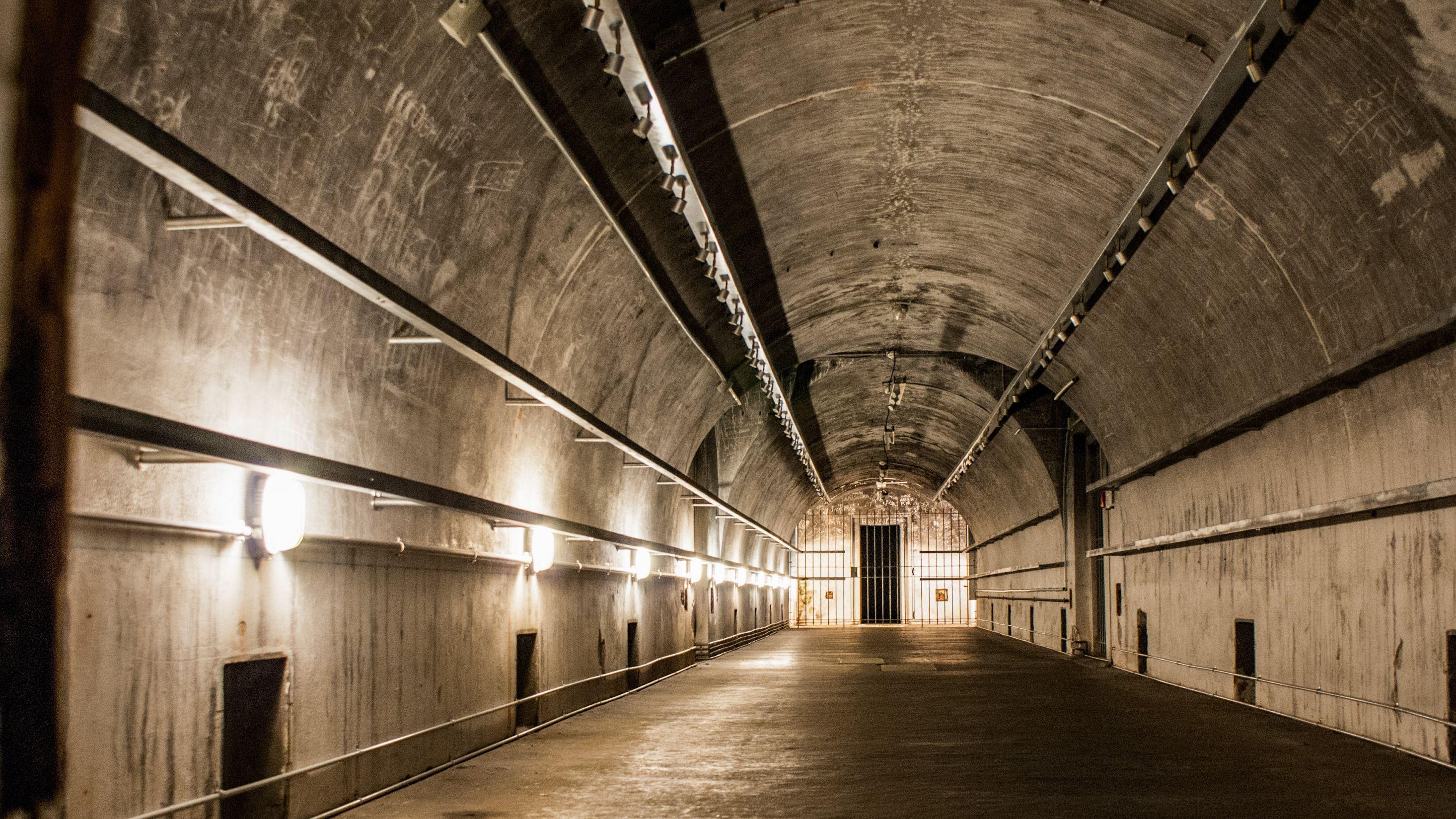 Innenansicht der Bunkeranlage Obersalzberg: Ein Betongewölbe mit einem Gitter am Ende des Ganges. An den Wänden sind verblasste Schriftzüge zu erkennen.
