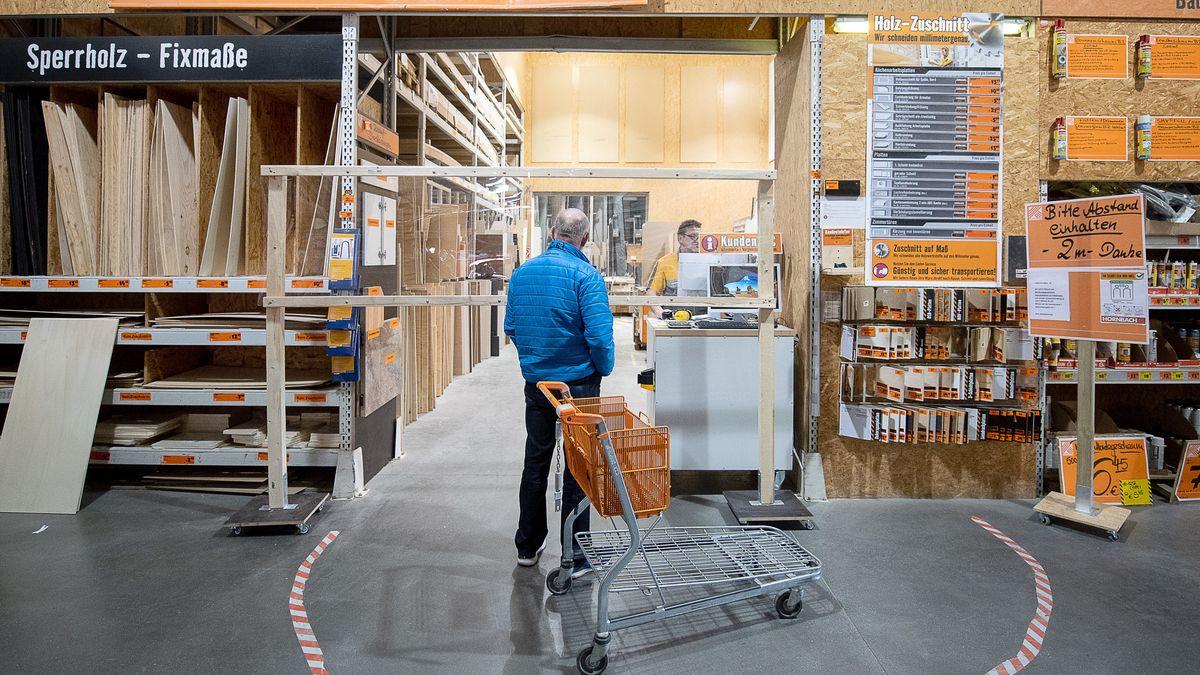 Ein Mann steht mit Einkaufwagen in einem Baumarkt und lässt sich von einem Mitabeiter beraten.