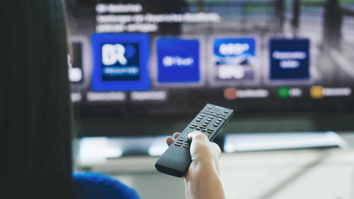 Eine Frau bedient ein Smart-TV