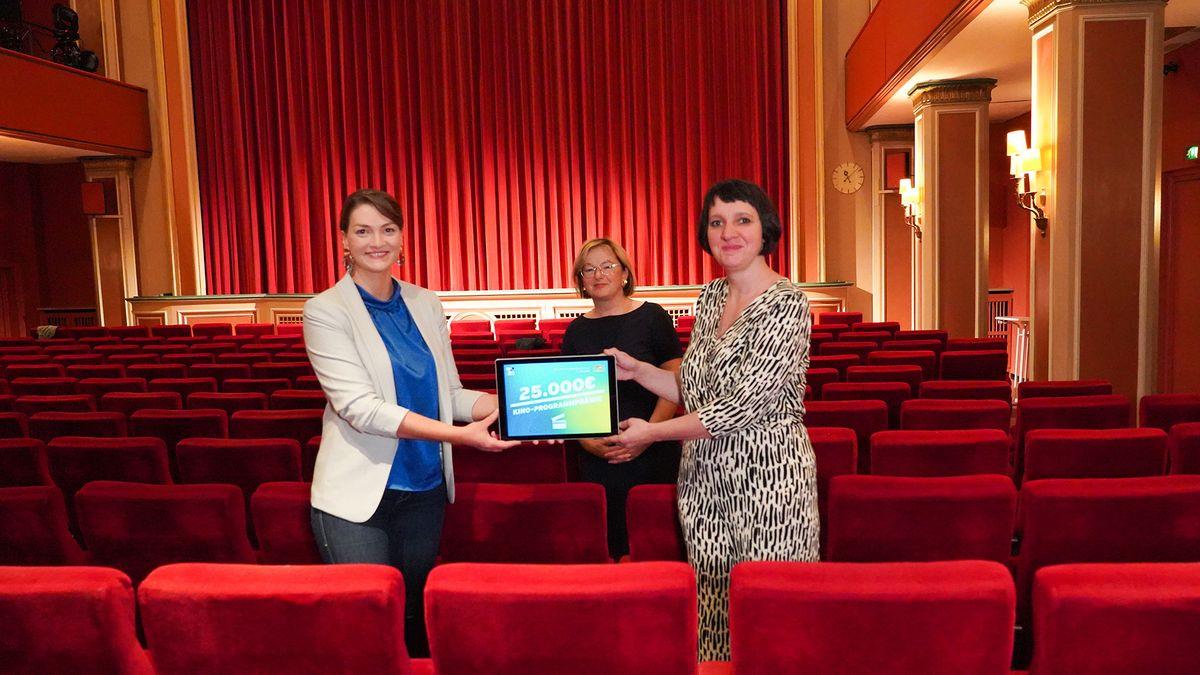 Digitalministerin Judith Gerlach, FFF-Geschäftsführerin Dorothee Erpenstein, Diana Linz vom Lichtspiel Bamberg stehen im roten Kinosaal mit der 25.000 Euro Prämie.