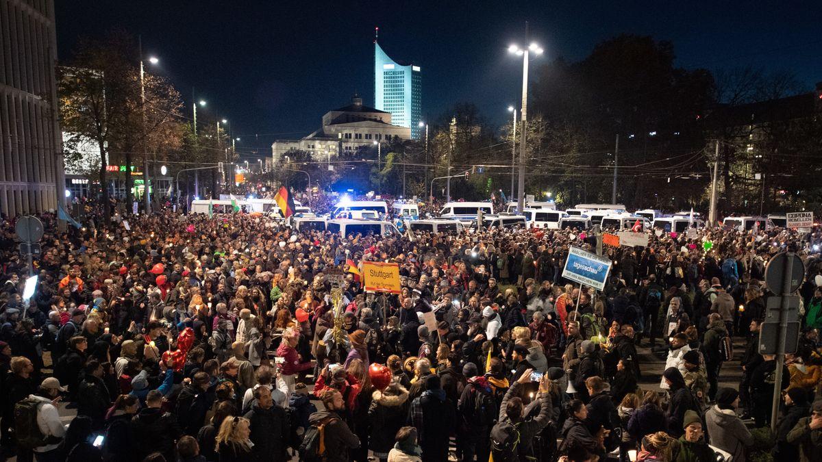 """Demonstranten der Stuttgarter Initiative """"Querdenken"""" stehen umgeben von Einsatzfahrzeugen der Polizei am Leipziger Hauptbahnhof"""