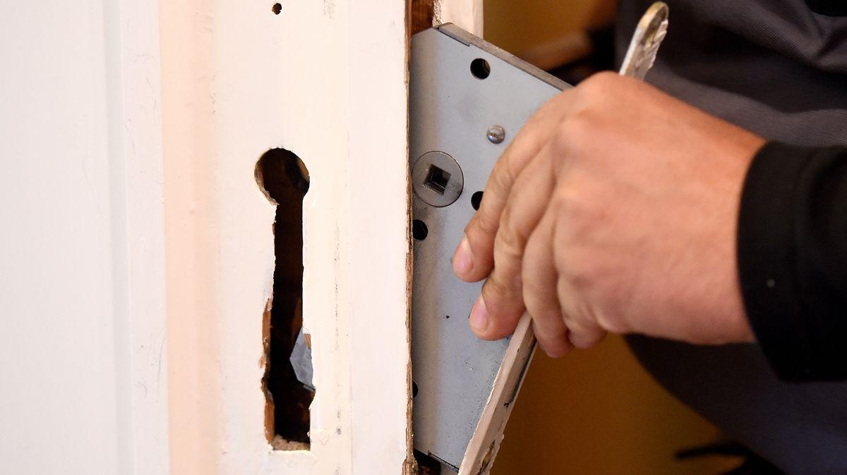 Schlüsseldienst baut ein defektes Türschloss aus (Symbolbild)