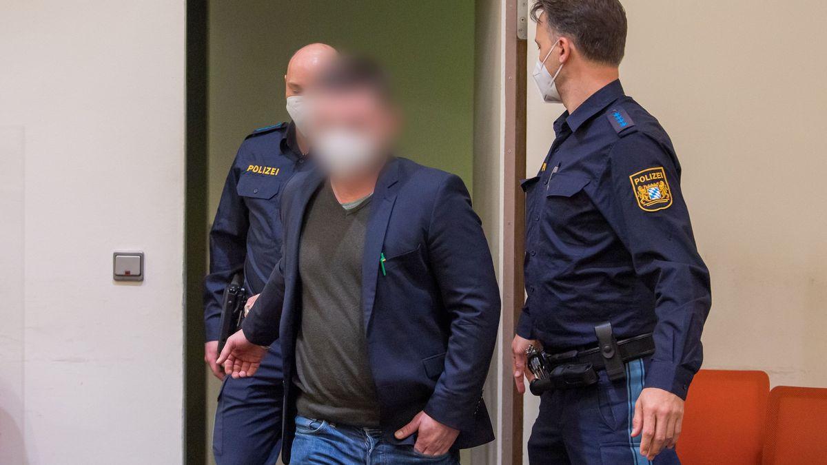 Der Angeklagte wird von Polizisten in den Verhandlungssaal geführt.