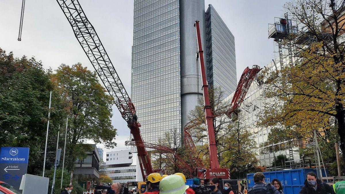 Der abgestürzte Ausleger des Krans liegt auf einem Hausdach im Arabellapark in München.