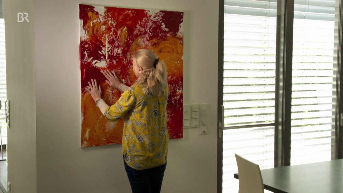 Die Künstlerin tastet das Bild mit den roten und orangenen Mustern in ihrer Wohnung ab.
