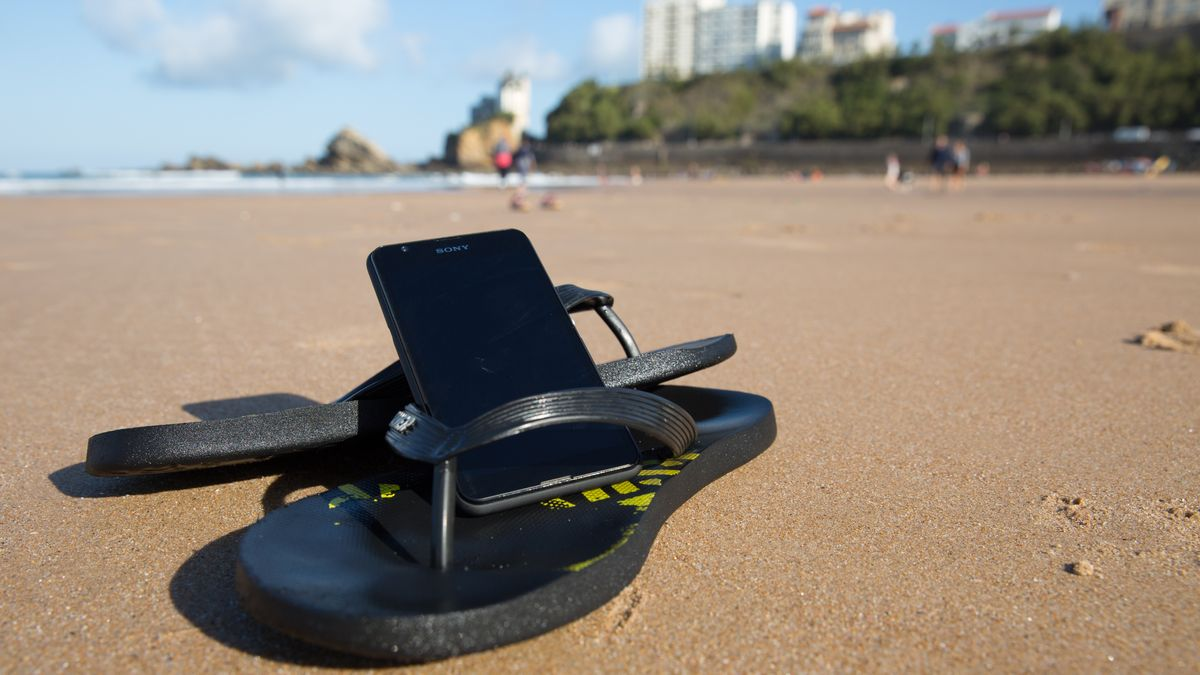 Symbolfoto: Ein Smartphone liegt in der Sonne am Strand.