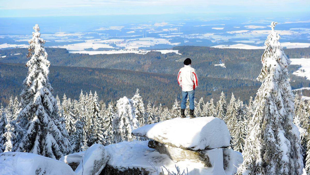 Ein Mann blickt vom Ochsenkopf bei Bischofsgrün über das Fichtelgebirge.