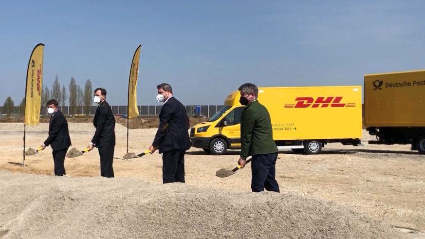 Vier Männer in Anzügen und FFP2-Masken, darunter Ministerpräsident Markus Söder, stehen mit kiesgefüllten Spaten auf einem Kiesfeld bei Aschheim, direkt an der A99. Im Hintergrund zwei gelbe Lastwagen mit den Logos der Deutschen Post und DHL.