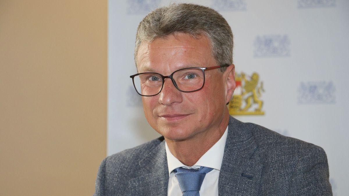 Porträt des Kunstministers vor bayerischem Wappen