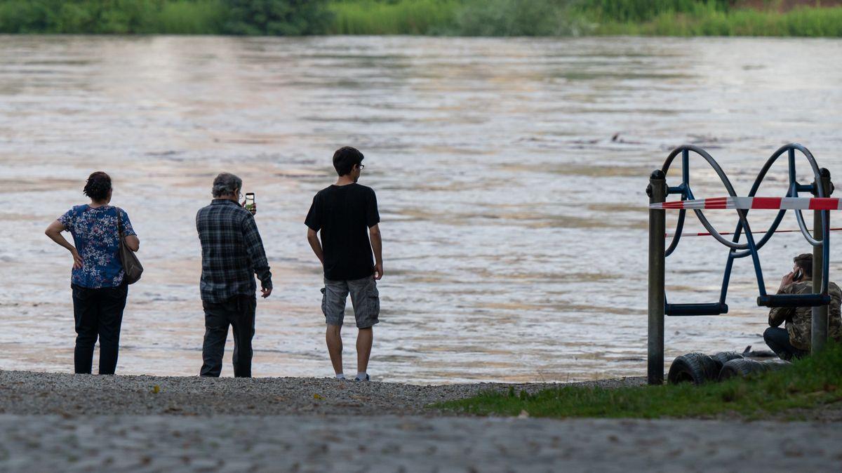 Passanten stehen Abend am teilweise überfluteten Ufer des Inn.