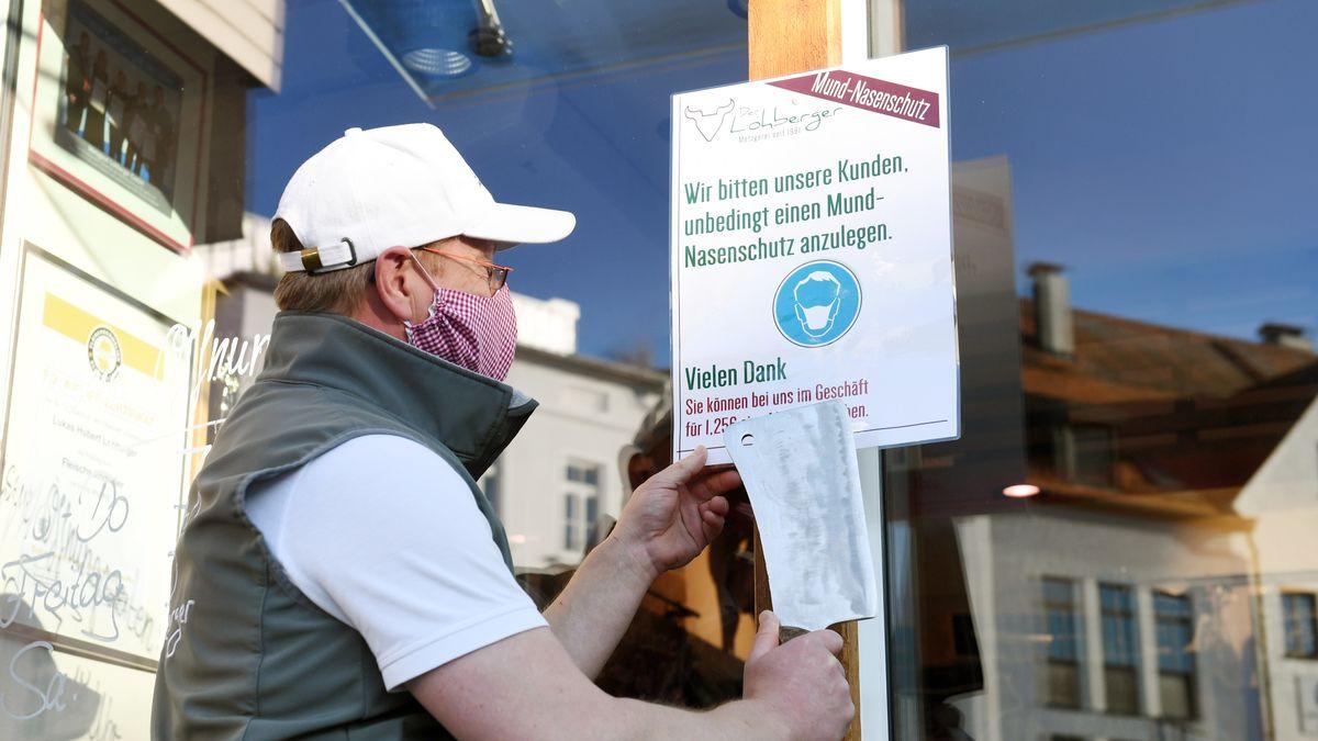 Inhaber einer Metzgerei in Rosenheim befestigt einen Aushang, der auf die Maskenpflicht hinweist.