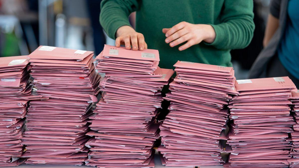 Wahlhelfer bereiten in einer Messehalle die Auszählung der Briefwahl vor.