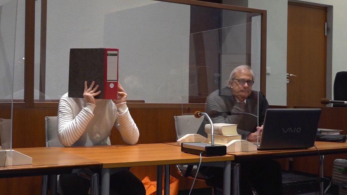 Der Angeklagte sitzt im Gerichtssaal und hält einen Ordner vor sein Gesicht.