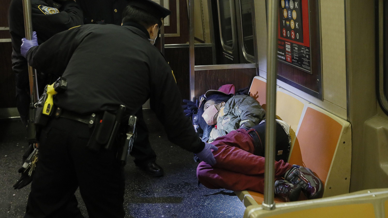 Polizisten wecken eine Passagierin in einer U-Bahn in Manhattan/New York