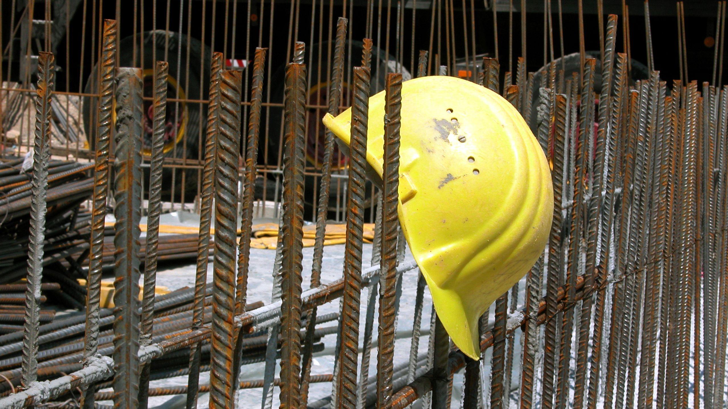 Ein gelber Bauhelm auf einer Stange, aufgenommen auf einer Baustelle (Symbolbild)