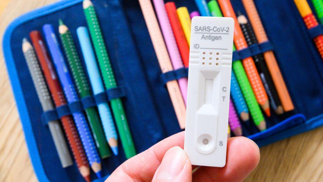 Eine Person hält einen Selbsttest in der Hand, im Hintergrund ist ein Federmäppchen mit Buntstiften zu sehen.