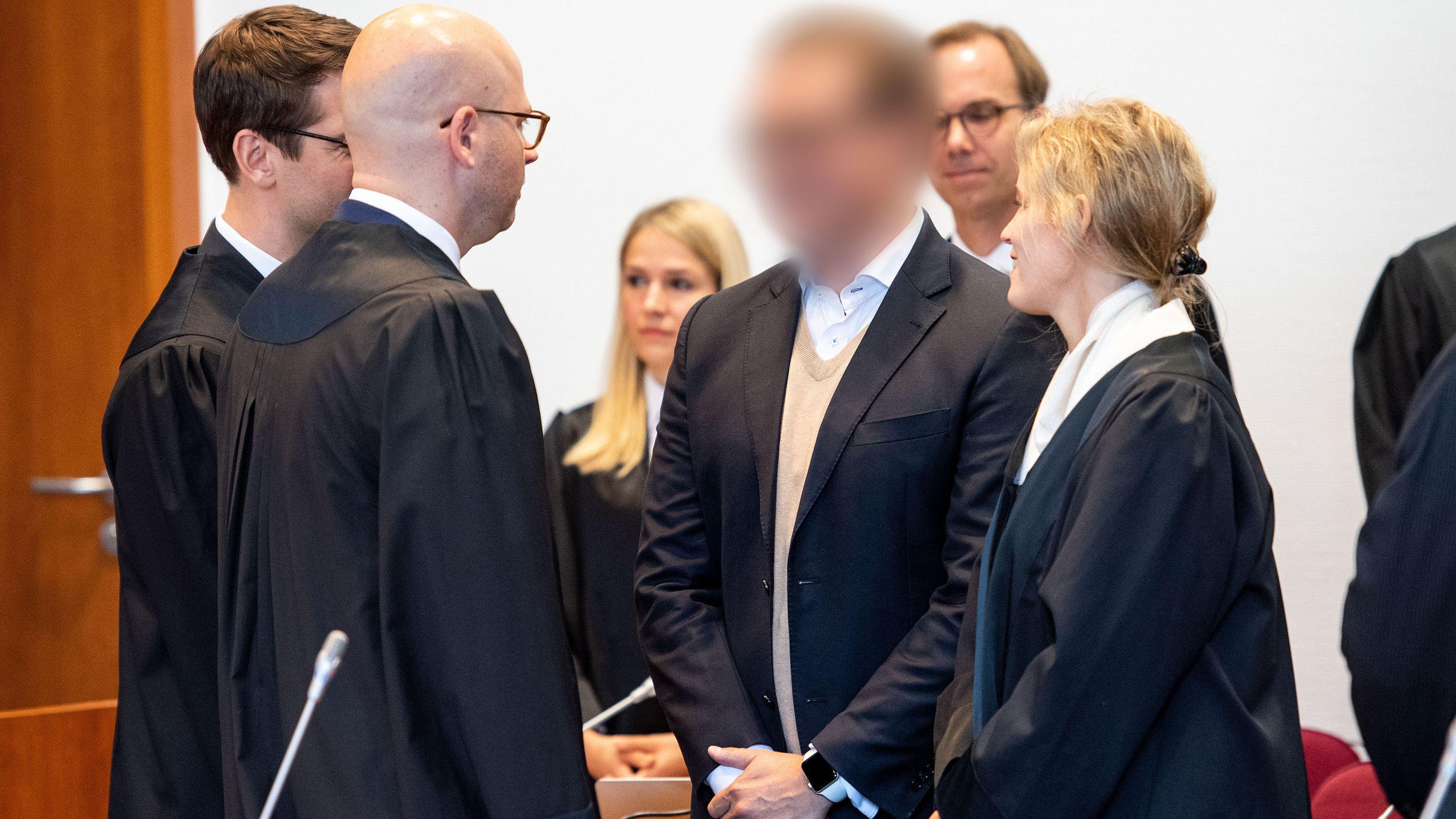 Einer der Angeklagten steht zusammen mit seinen Verteidigern, Übersetzern und Vertretern verschiedener Banken im Landgericht hinter der Anklagebank